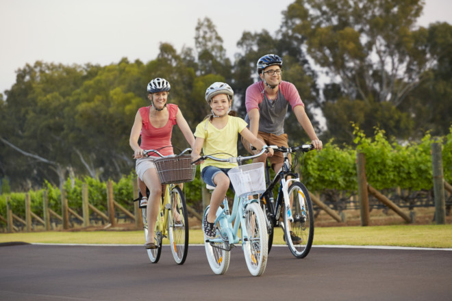 Family cycling past vines